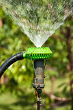Sprinkler spraying water over green grass Royalty Free Stock Photos