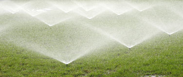 Sprinkler spraying water over green grass Royalty Free Stock Images