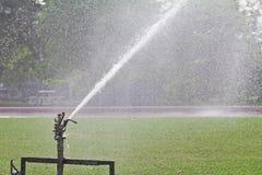 Sprinkler spraying water over lawn Stock Photos