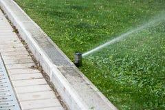Sprinkler system working on fresh green grass Royalty Free Stock Photos