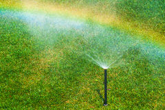 Sprinkler tube and a rainbow 2 Stock Photography