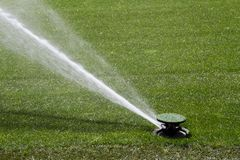 Sprinkler washing green grasses Royalty Free Stock Images
