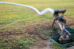 Sprinkler and water hose in grass field football stadium Stock Photo