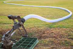 Sprinkler and water hose in grass field football stadium Stock Photos