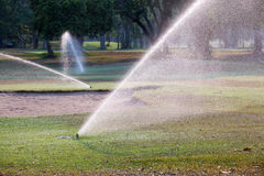 Sprinkler watering in golf course Stock Photos