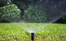 Sprinkler watering the lawn in a park, bokeh background. Royalty Free Stock Photos