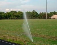 Sprinkleranlage, die unten zu einem Lauf, außerhalb der Saison Feld an einem Highschool Stadion neigt lizenzfreie stockfotografie