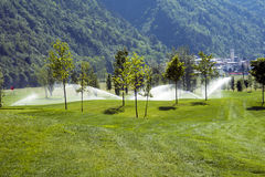Sprinklers on golf course Royalty Free Stock Images