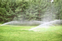 Sprinklers at golf course Royalty Free Stock Photos