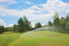 Sprinklers at golf course Royalty Free Stock Image