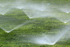 Sprinklers on a green lawn. Sprinklers on a fresh green lawn Stock Photos