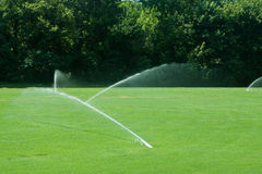 Sprinklers irrigating a green grass field Royalty Free Stock Images