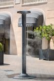 Sprinklers splashing vaporized water at street in order to cool the hot summer temperature Stock Photo