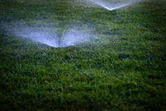 Sprinklers Spraying Water on Lawn Grass Stock Photography