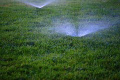 Sprinklers Spraying Water onto Lush Green Grass. Lawn Stock Photography