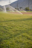 Sprinklers watering field. Several baseball field sprinklers are wartering the grass with mountains in the background Stock Photos