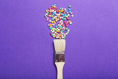 Sprinkles. Colorful sprinkles with paintbrush on the purple background Royalty Free Stock Images