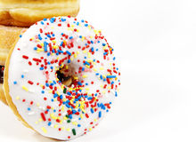 Sprinkles Doughnut. A doughnut with white frosting and colorful sprinkles turned on edge and leaning against stacked doughnuts, white background Stock Photo