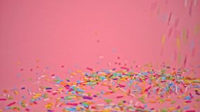 Sprinkles falling on pink background, decoration for cake and bakery, slow motion stock video
