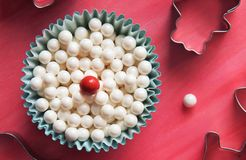 Sprinkles pearls of beige color in cup on pink background. Top view Stock Photos