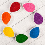 Sprinkles. A rainbow assortment of colorful baking sprinkles used for decorating cookies and cakes in petal shaped bowls stock image