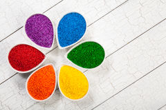 Sprinkles. A rainbow assortment of colorful baking sprinkles used for decorating cookies and cakes in petal shaped bowls stock photos