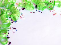 Sprinkles and Spirals. Green curling ribbon and candy sprinkles party theme with negative space to add your own text Royalty Free Stock Photography