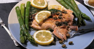 Sprinkling black pepper over a delicious roasted organic salmon stock video