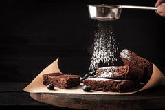 Sprinkling chocolate brownie with icing sugar Stock Photography