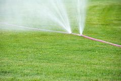 Sprinkling on grass from damaged hose Stock Photos