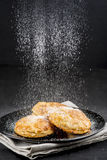 Sprinkling powdered sugar on cakes Stock Images
