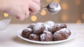 Sprinkling powdered sugar on chocolate cookies crinkles. chocolate cookies with powdered sugar. Sifting powdered sugar on the top. Sprinkling powdered sugar on stock video footage
