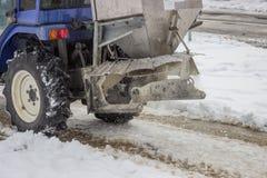 Sprinkling salt on a sidewalk after snowfall 2 Royalty Free Stock Images