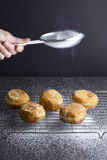 Sprinkling sugar on jam doughnuts Stock Photography