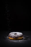 Sprinkling sugar powder on chocolate donut Stock Photography