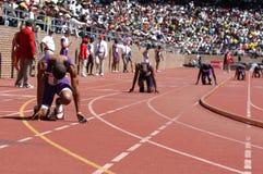 sprintar klara relaylöpare för race start till Arkivfoto