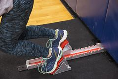 Sprinter in the blocks for speed training indoor in the gym. A sprinter getting sprint start practice using the starting blocks at night in the high school gym Stock Photo