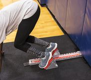 Sprinter in the blocks training indoors. A high school sprinter practicing coming out of the blocks during an indoor practice seccion in a gymnasium Stock Photos