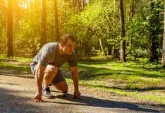 Sprinter caucasico risoluto che prepara iniziare a correre sulla strada in parco Corridore dell'uomo sulla posizione di inizio Sp fotografia stock libera da diritti