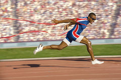 Sprinter Crossing the Finish Line. African American sprinter crossing the finish line and breaking the tap. Horizontally framed shot Stock Photography