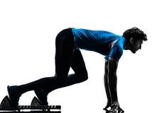 Sprinter de coureur d'homme sur les blocs commençants  silhouette photographie stock