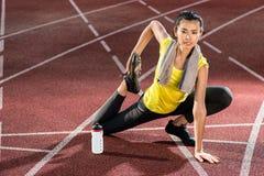 Sprinter della donna che fa esercizio di riscaldamento prima dello sprint Fotografia Stock