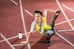 Sprinter della donna che fa esercizio di riscaldamento prima dello sprint Fotografia Stock Libera da Diritti