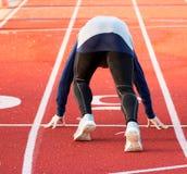 Sprinter in der Satzposition auf einer roten Bahn lizenzfreie stockfotografie