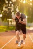 Sprinter, der Startblöcke auf der Laufbahn lässt Explosiver Anfang Stockbilder