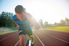 Sprinter, der Startblöcke auf der Laufbahn lässt Explosiver Anfang Stockbild