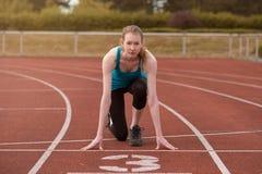 Sprinter för ung kvinna i startknapppositionen royaltyfria foton