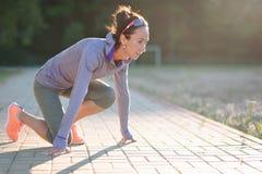 Sprinter girl start position on the track. Jogging sport. The Sprinter girl start position on the track. Jogging sport Stock Images