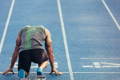 Sprinter on his marks on a running track. Rear view of an athlete ready to sprint on an all-weather running track. Runner using a starting block to start his run Stock Image