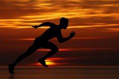 Sprinter man. Man running at full speed at sunset Royalty Free Stock Images